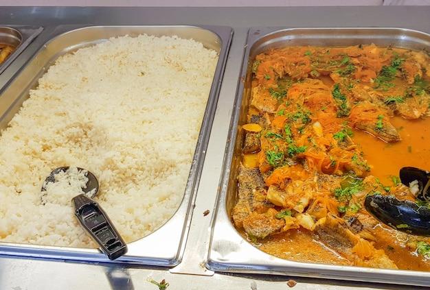 Buffet di primo piano con pesce e carote sott'aceto e riso a parte.