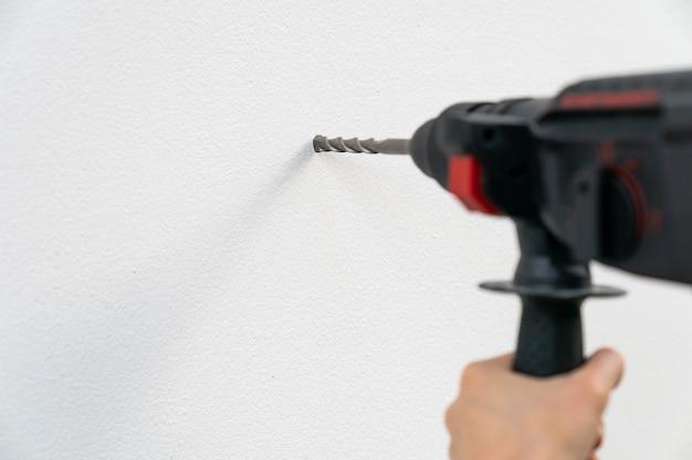 Chiuda sulla perforazione della mano del costruttore o dell'operaio con una macchina sulla parete bianca.
