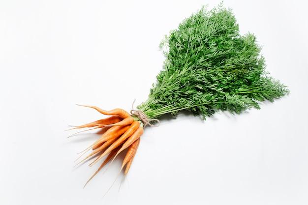 Close-up di mazzo di carote legate con una corda su sfondo bianco. vista dall'alto.
