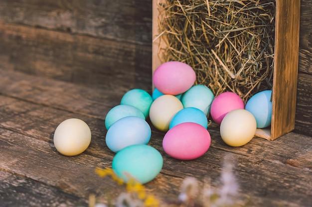 Primo piano, un mucchio di uova con fieno sullo sfondo di una tavola d'epoca.