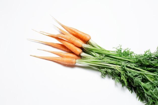Close-up di mazzo di carote fresche su sfondo bianco.