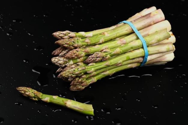 Close up mazzetto di asparagi verdi freschi lavati sulla tavola nera con gocce d'acqua, ad alto angolo di visione