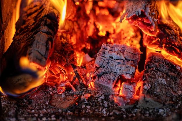Primo piano di un fuoco ardente in un caminetto in mattoni. legna da ardere di betulla. casa.
