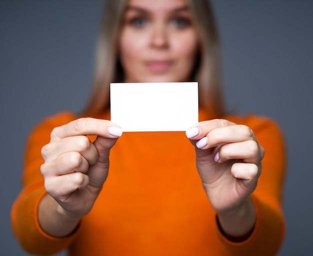 Primo piano biglietto da visita nelle mani delle donne con effetto bokeh e copia spazio per mockup di carta.