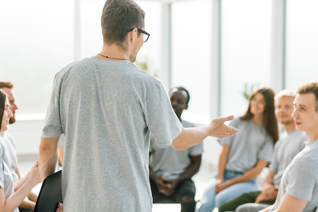 Avvicinamento. business coach tiene un dibattito con un gruppo di giovani. affari e istruzione