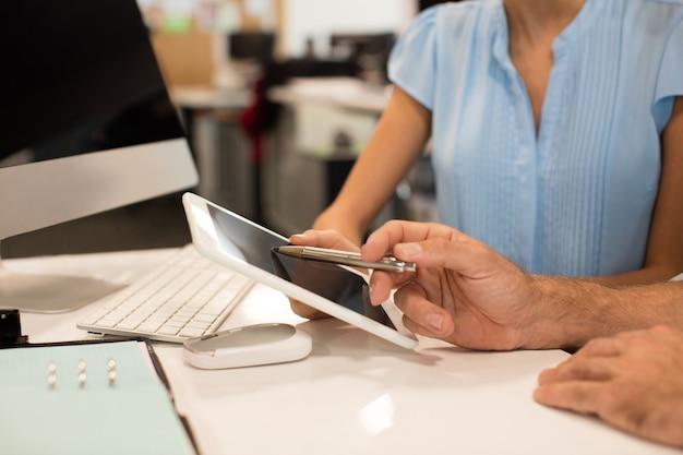 Chiuda in su dei colleghi di lavoro che discutono sulla tavoletta digitale