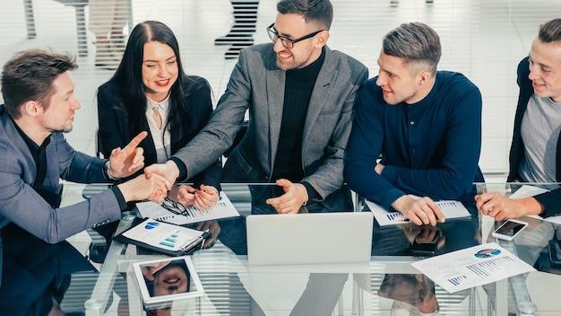 Avvicinamento. colleghi di lavoro che agitano le mani su un ufficio scrivania. concetto di affari.