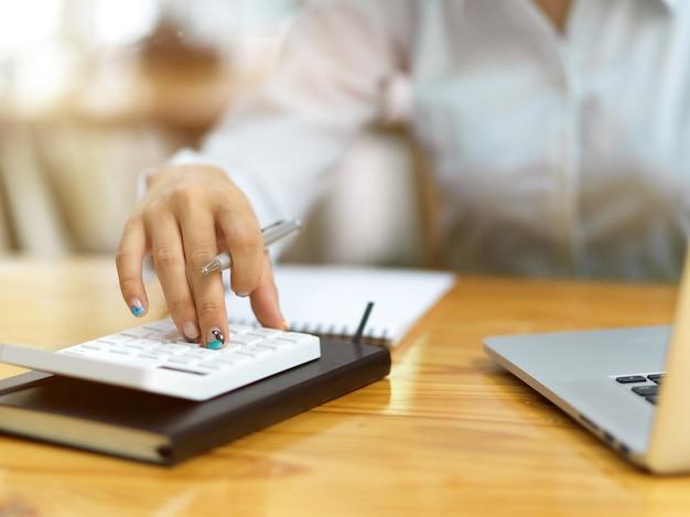 Primo piano delle dita femminili aziendali utilizzando la calcolatrice in ufficio, contabile che calcola l'utile netto