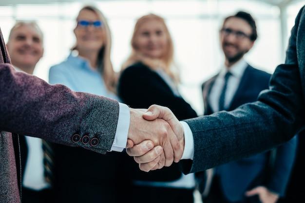 Avvicinamento. stretta di mano di affari su uno sfondo di ufficio. concetto di affari