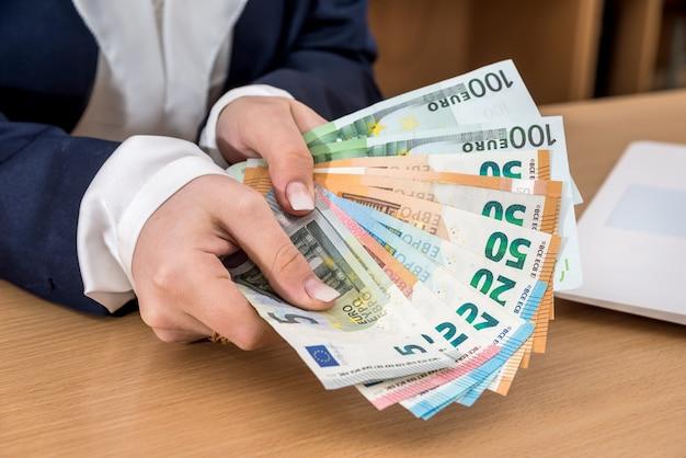 Primo piano della signora di affari che deduce l'euro e la calcolatrice