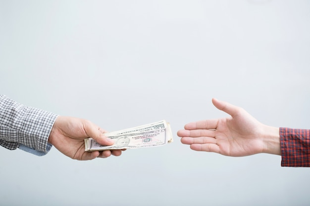 Chiuda sulla mano dell'uomo di affari che tiene dando soldi isolati