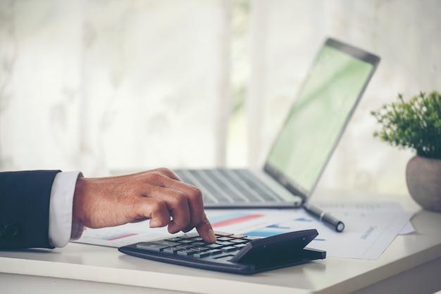 Chiudere le mani dell'uomo d'affari utilizzando la calcolatrice che conta il conto finanziario delle tasse audit fiscale concetto finanziario