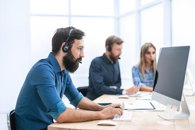 Avvicinamento. uomo d'affari in un auricolare lavorando su un computer in ufficio