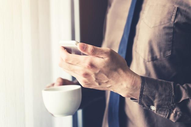 Close up uomo d'affari azienda smartphone e caffè in ufficio con la luce del sole. filtro tonico vintage.