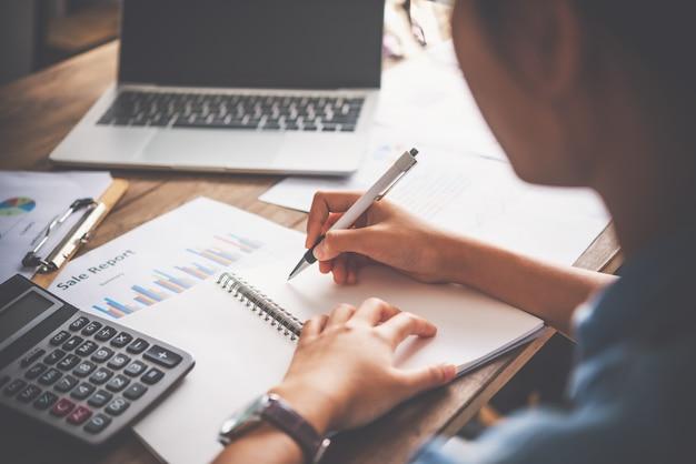 Primo piano di un uomo d'affari seduto a una scrivania in ufficio. analisi e pianificazione del concetto di business