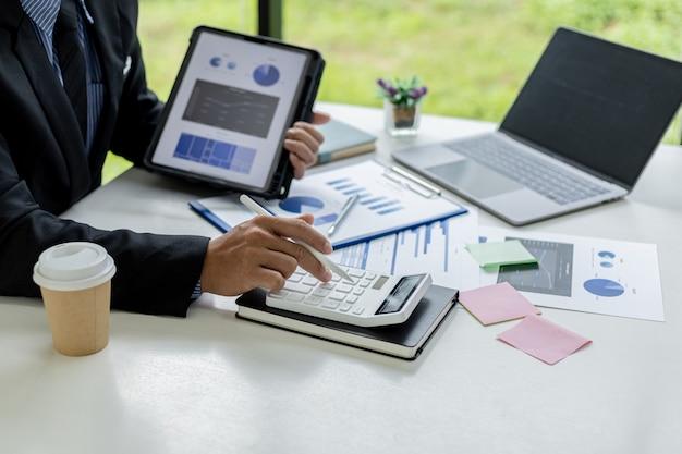 Primo piano di un uomo d'affari che utilizza una calcolatrice bianca, un uomo d'affari finanziario che esamina i dati numerici su un documento finanziario aziendale, utilizza una calcolatrice per verificare l'accuratezza dei numeri.