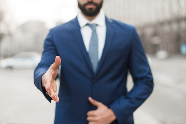 Uomo di affari del primo piano con la mano pronta per la scossa