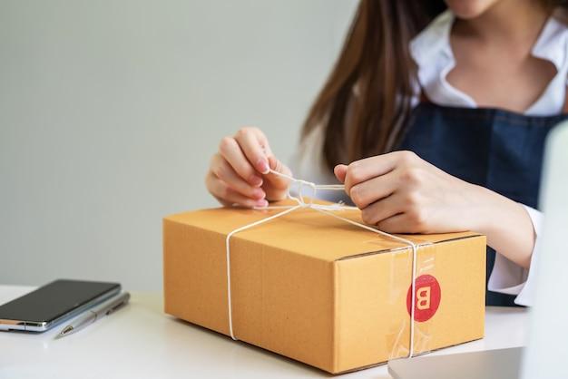 Primo piano dei pacchi di imballaggio a mano dell'imprenditore da consegnare ai clienti a casa.