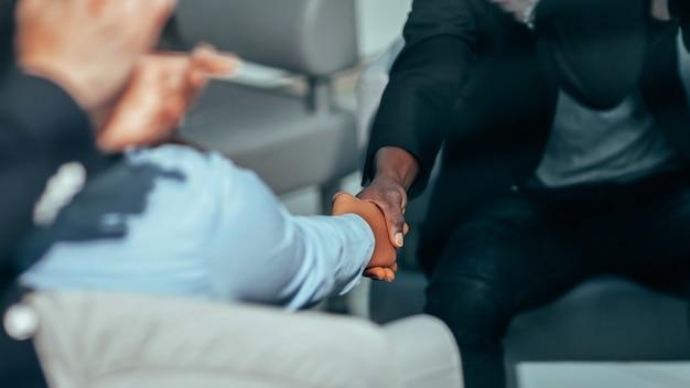 Avvicinamento. uomini d'affari che si salutano in ufficio. sfondo di affari
