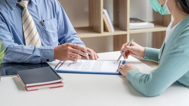 Primo piano delle mani di uomini d'affari che fanno contratto insieme in ufficio.
