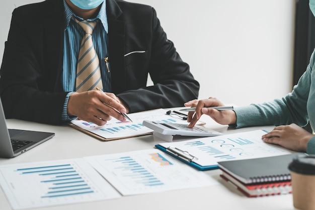 Primo piano di uomini d'affari che si incontrano in possesso di una penna utilizzando la calcolatrice e il grafico di puntamento collocato in ufficio.