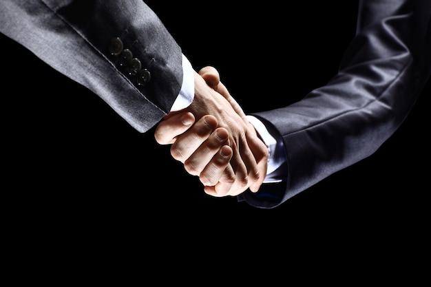 Primo piano di uomini d'affari che si stringono la mano per confermare la loro partnership
