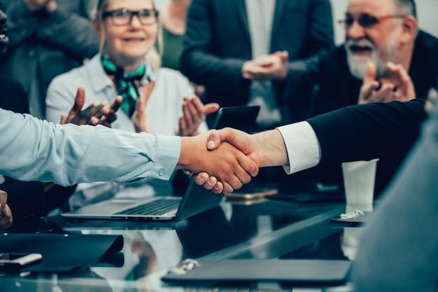 Avvicinamento. il team aziendale applaude durante i negoziati. il concetto di cooperazione