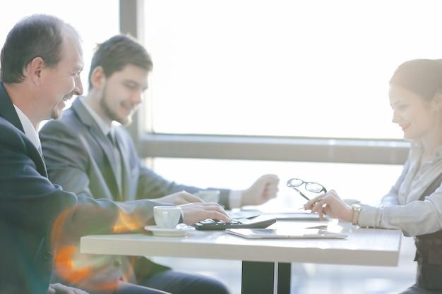 Primo piano.il team aziendale considera il profitto utilizzando la calcolatrice.contabilità