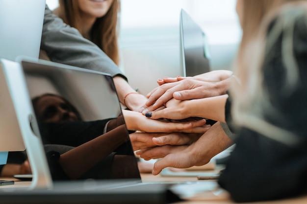 Primo piano del team aziendale che unisce le mani sulla scrivania