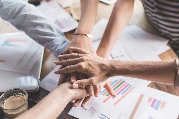 Primo piano di squadra di affari che mostra l'unità con le loro mani insieme