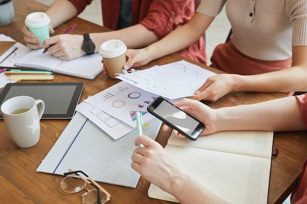 Primo piano della squadra di affari che si siede al tavolo e lavoro di pianificazione insieme durante la riunione d'affari in ufficio