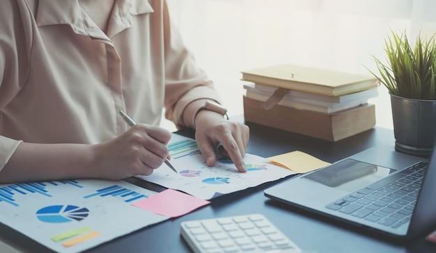Primo piano donna d'affari che controlla un grafico su una scrivania di legno in ufficio
