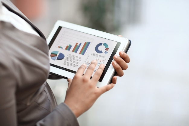 Avvicinamento. donna d'affari controlla il rapporto finanziario utilizzando la tavoletta digitale.