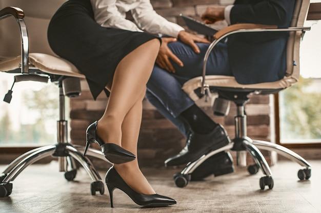 Chiuda sulla donna di affari che flirta con l'uomo in ufficio