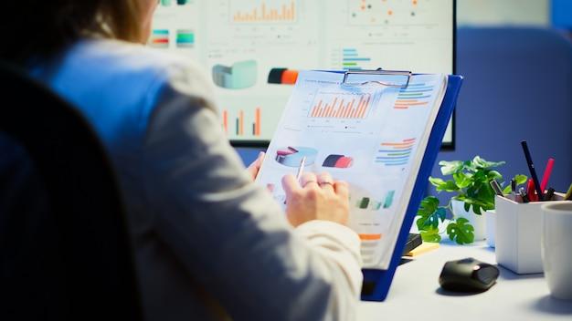 Primo piano di donna d'affari che tiene appunti con grafici e statistiche finanziarie che fa gli straordinari davanti al computer seduto nell'ufficio di start-up. impiegato impegnato che utilizza la tecnologia moderna