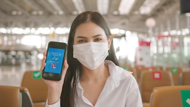 Close up una donna d'affari indossa una maschera protettiva in aeroporto internazionale, mostrando il passaporto del vaccino sul suo smartphone, viaggi sotto il concetto covid-19