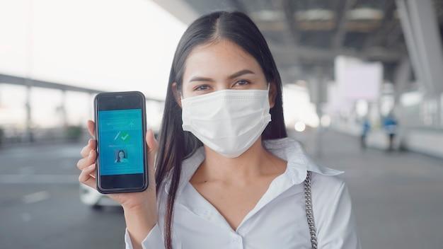 Primo piano di donna d'affari indossa una maschera protettiva in aeroporto internazionale, mostrando il passaporto del vaccino sul suo smartphone