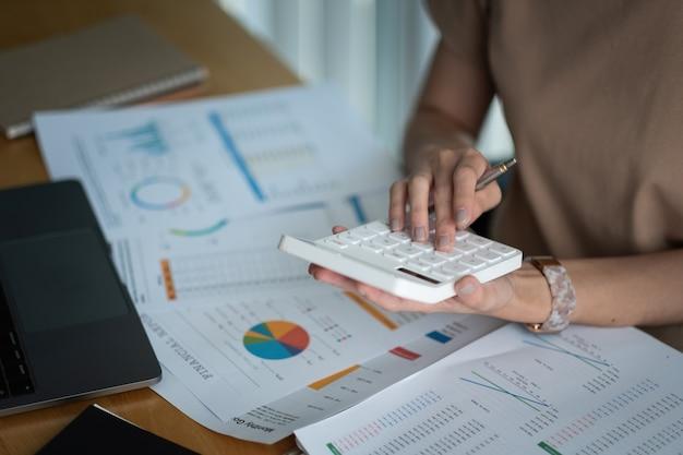 Primo piano donna d'affari che utilizza calcolatrice e laptop per fare finanza matematica sulla scrivania in legno in ufficio e sfondo di lavoro aziendale, tasse, contabilità, statistiche e concetto di ricerca analitica.