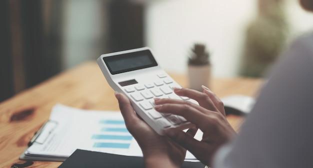 Primo piano donna d'affari che utilizza calcolatrice e laptop per fare finanza matematica sulla scrivania di legno in ufficio e sfondo di lavoro aziendale, tasse, contabilità, statistiche e concetto di ricerca analitica