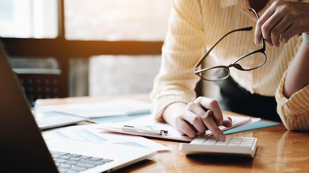 Chiuda sulla donna di affari che per mezzo del calcolatore e del computer portatile per finanzi la matematica sullo scrittorio di legno