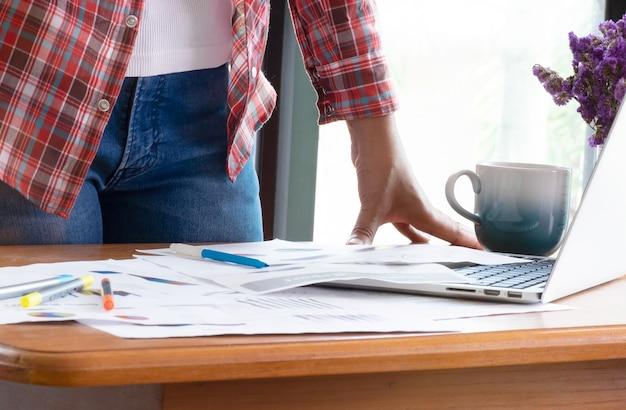 Chiuda sulla donna di affari che lavora nell'ufficio e prenda la decisione sulle statistiche del rapporto di vendita