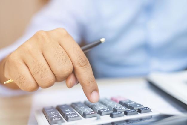 Close up imprenditore o ragioniere mano azienda matita lavorando sulla calcolatrice per calcolare il rapporto sui dati finanziari, documenti contabili e computer portatile in ufficio, concetto di affari