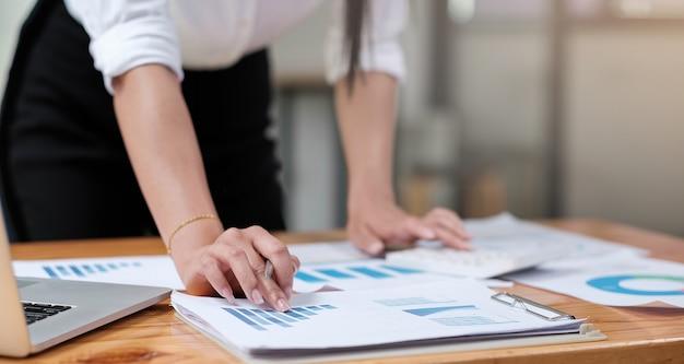 Primo piano della mano dell'uomo d'affari o del ragioniere che tiene la matita che lavora sulla calcolatrice per calcolare il rapporto sui dati finanziari, il documento contabile e il computer portatile in ufficio, il concetto di business