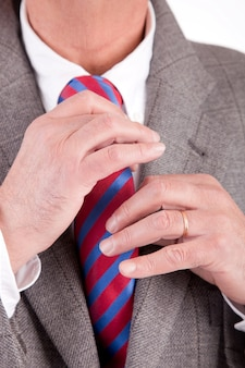 Primo piano su uomo d'affari che organizza la sua cravatta