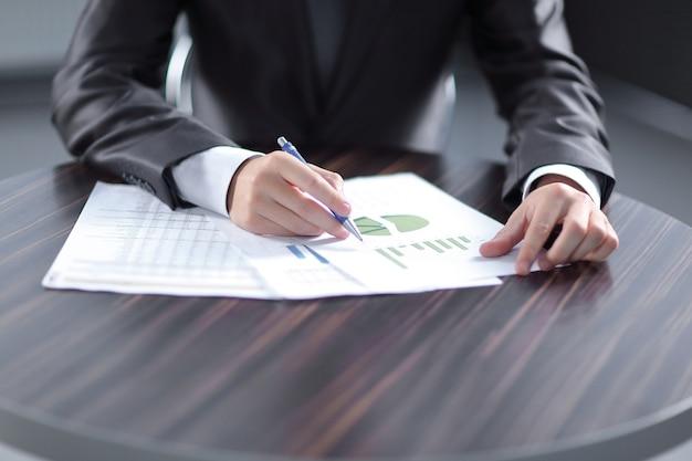 Primo piano dell'uomo d'affari che controlla i grafici finanziari che mostrano i risultati.