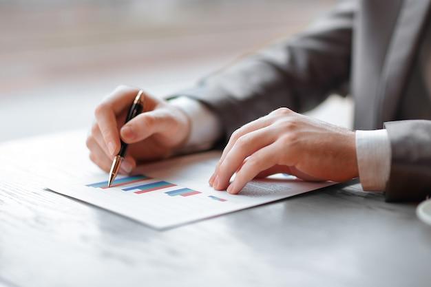 Primo piano.l'uomo d'affari controlla il profitto finanziario dell'azienda. concetto di business