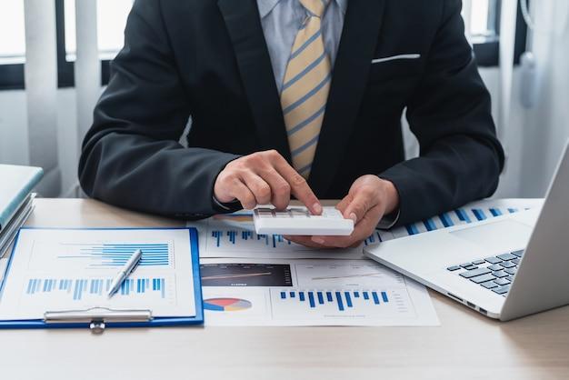 Primo piano di un uomo d'affari che fa calcoli utilizzando una calcolatrice del lavoro di contabilità in ufficio
