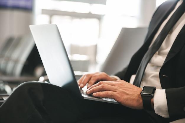 Close up di imprenditore vestito in tuta utilizzando laptop