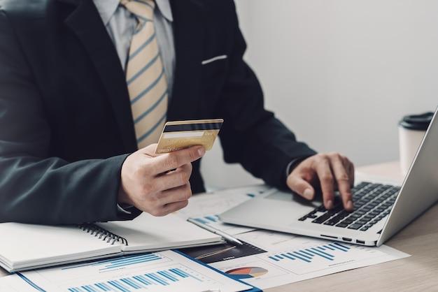 Primo piano della mano dell'uomo d'affari che tiene lo shopping online della carta di credito tramite il computer portatile con il grafico disposto all'ufficio.