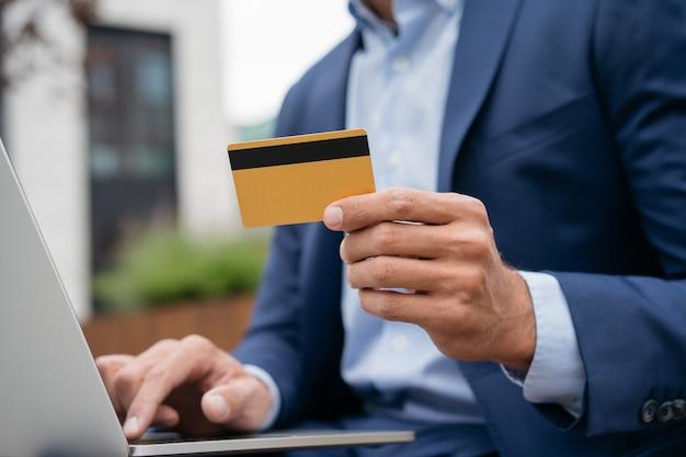 Primo piano della mano dell'uomo d'affari che tiene la carta di credito dorata che fa acquisti online facendo una prenotazione